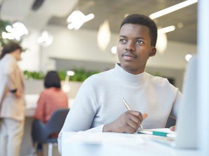 jovem a fazer pesquisa no computador e a tirar notas