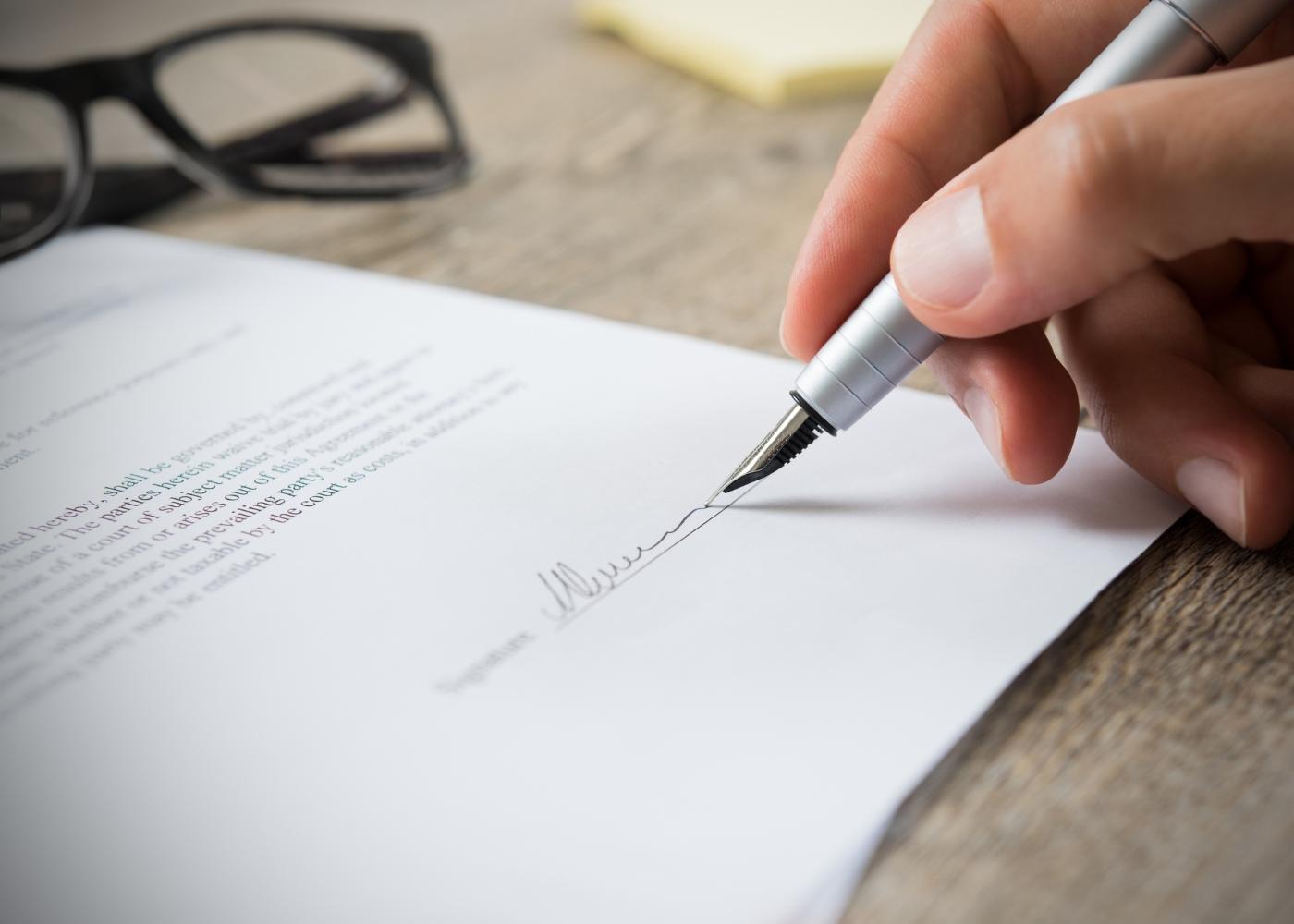 pessoa a assinar contrato de trabalho temporário