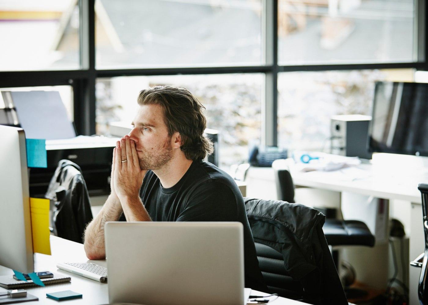 homem a trabalhar pensativo a considerar as resoluções de carreira