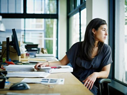 mulher no escritório a olhar pela janela pensativa