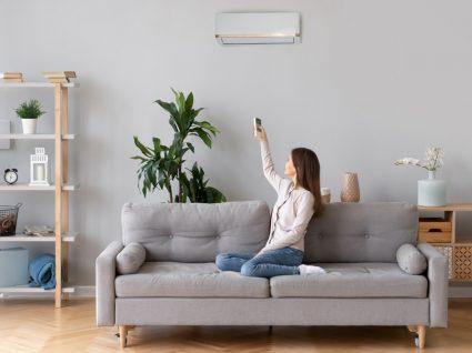 mulher no sofá a ligar o ar condicionado