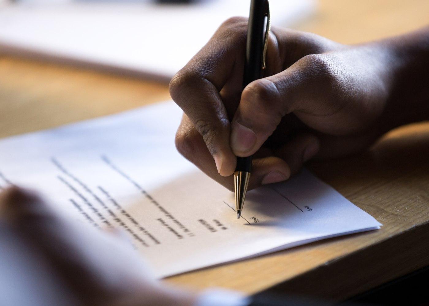 leis laborais: pessoa a assinar contrato