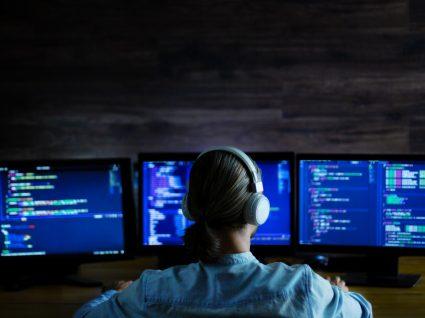 mulher com três monitores a programar
