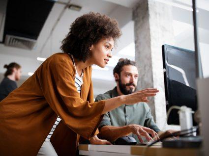 mulher a ajudar colega com trabalho no computador