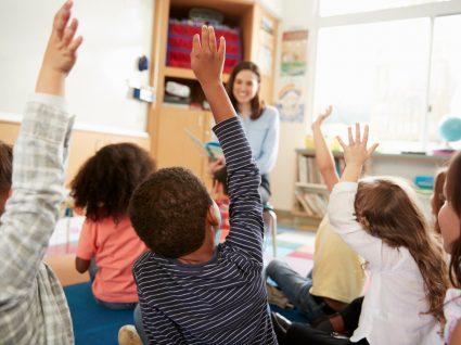 crianças na escola sentadas no chão com o braço no ar