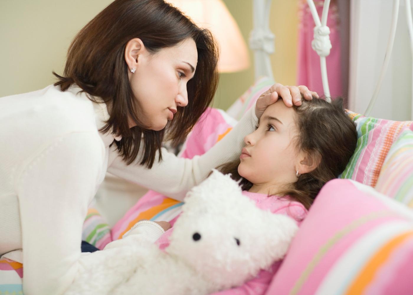mãe a medir a febre a filha doente