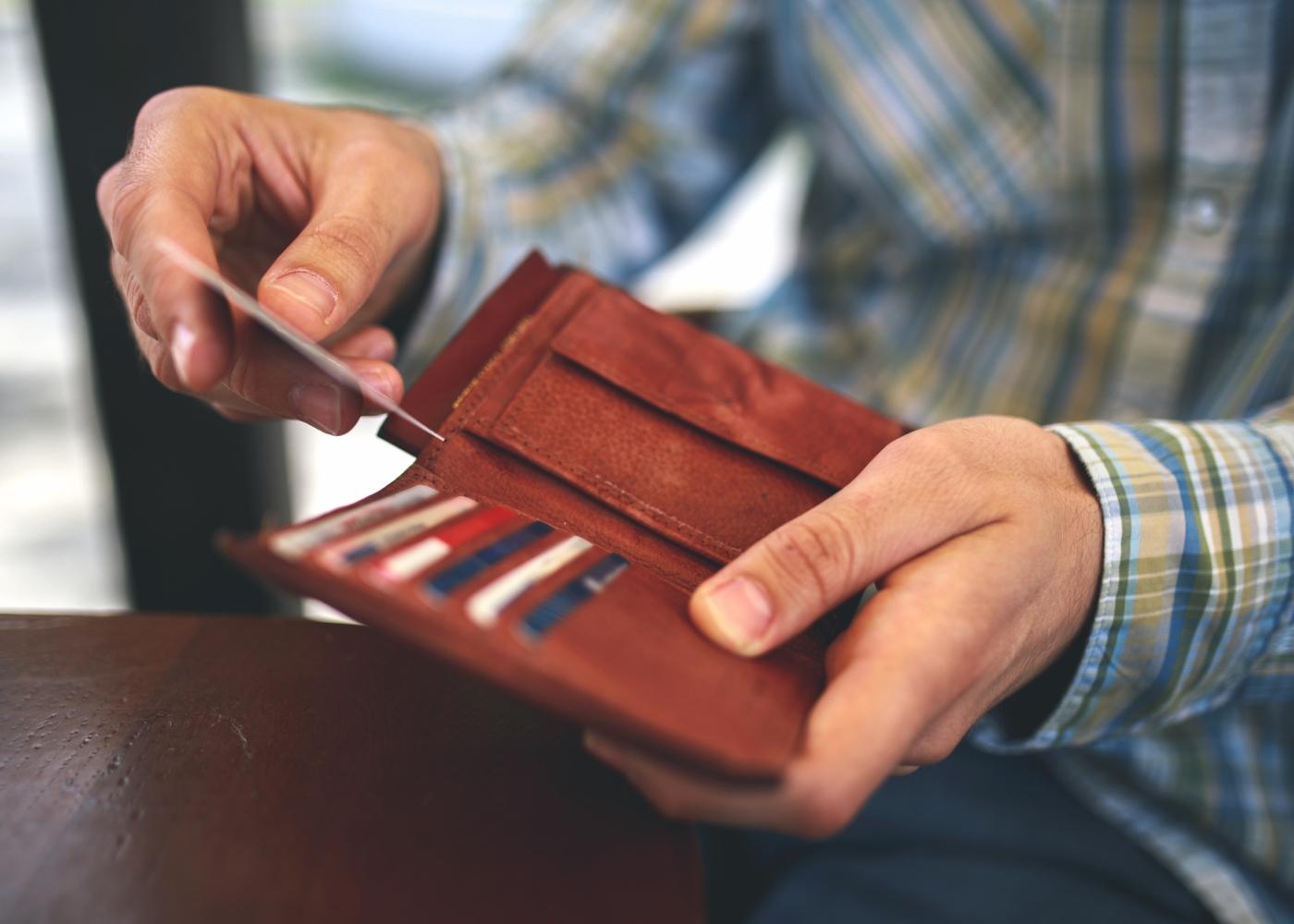 Homem a guardar cartões na carteira