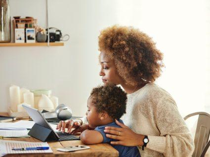 mãe com filho ao colo a pesquisar sobre a licença parental complementar