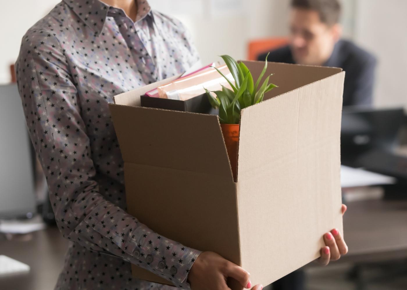 trabalhadora com caixa depois de ser despedida