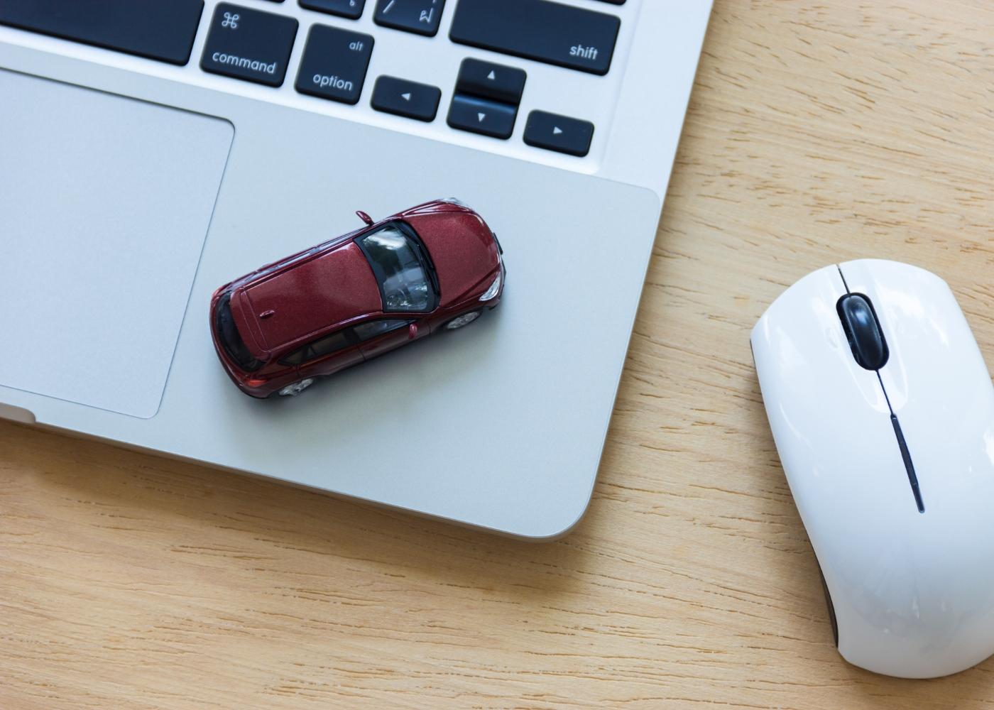 carro de brincar em cima de computador e rato