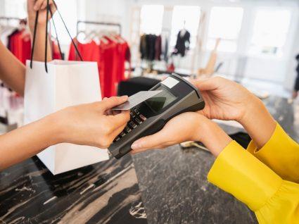 Mulher a pagar em loja e a gastar menos em roupa
