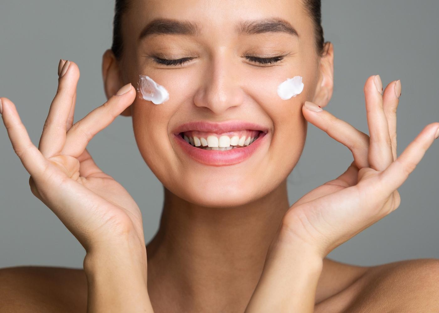 jovem sorridente a cuidar do seu rosto com creme hidratante