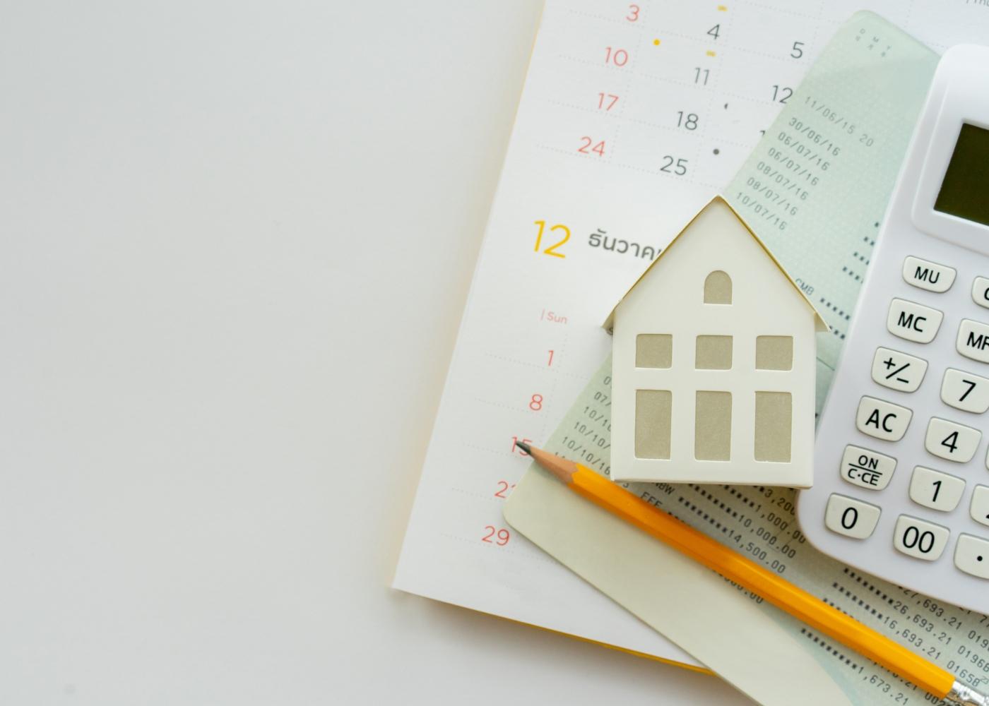 Calculadora, caderneta bancária e casa em miniatura para exemplificar o que é um crédito hipotecário