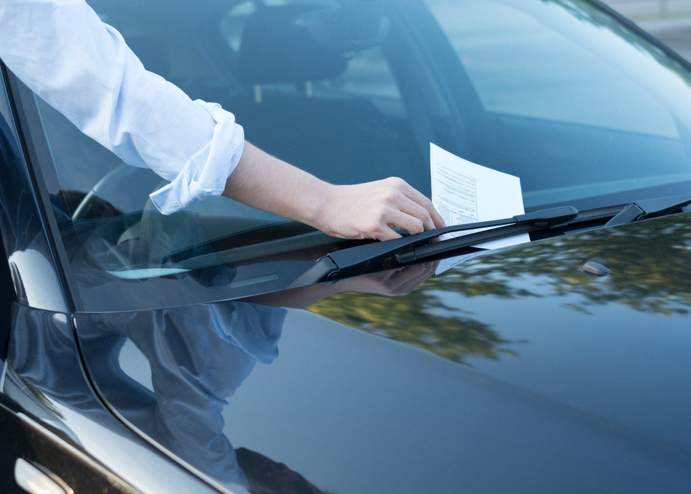 Homem a pegar em multa num carro
