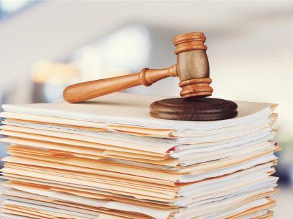 martelo de juiz em cima de um conjunto de processos empilhados
