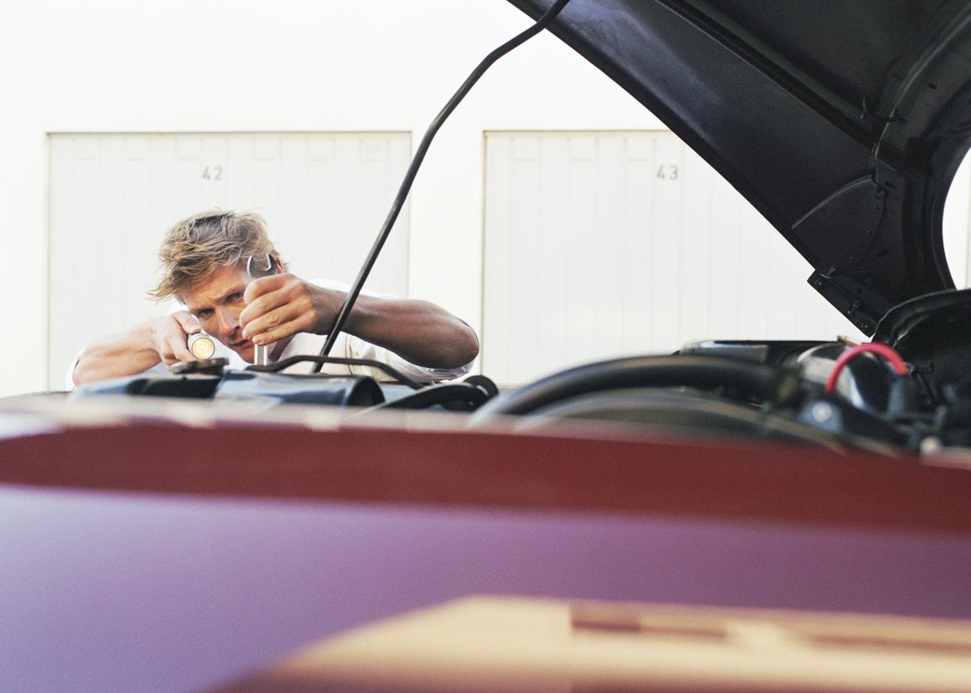 homem a reparar carro