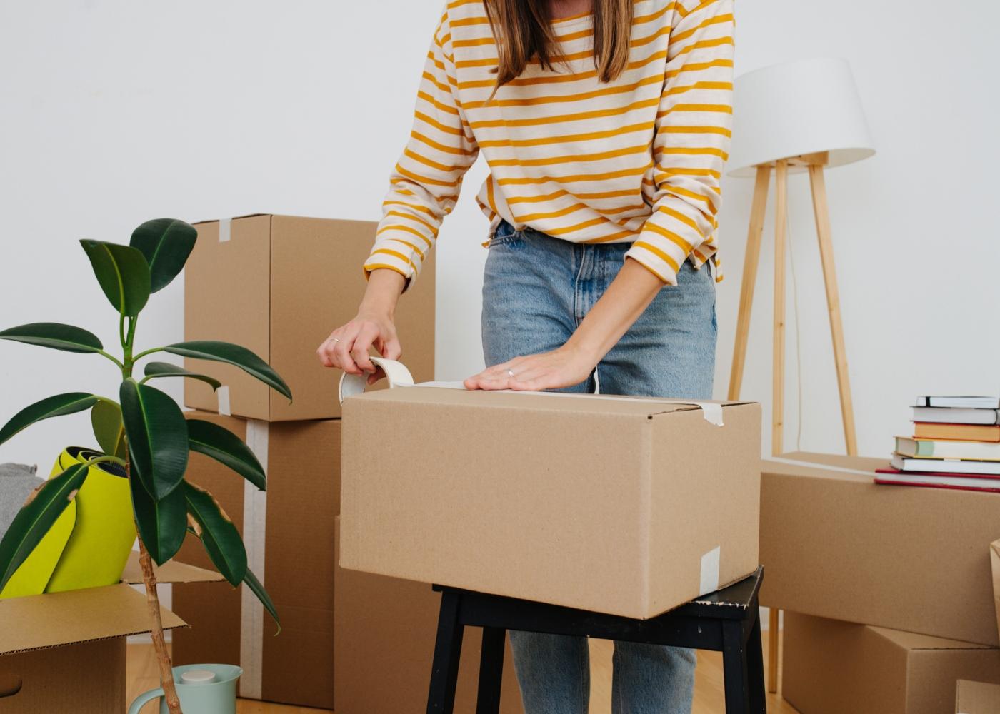 Mulher a encaixotar objetos pessoais durante mudança de casa