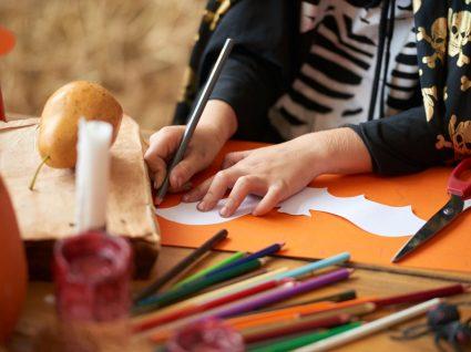 criança a preparar itens decorativos de halloween na escola