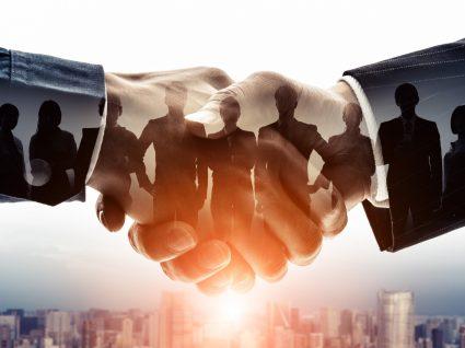 mãos a cumprimentar com sombra de pessoas a representar a organização internacional do trabalho
