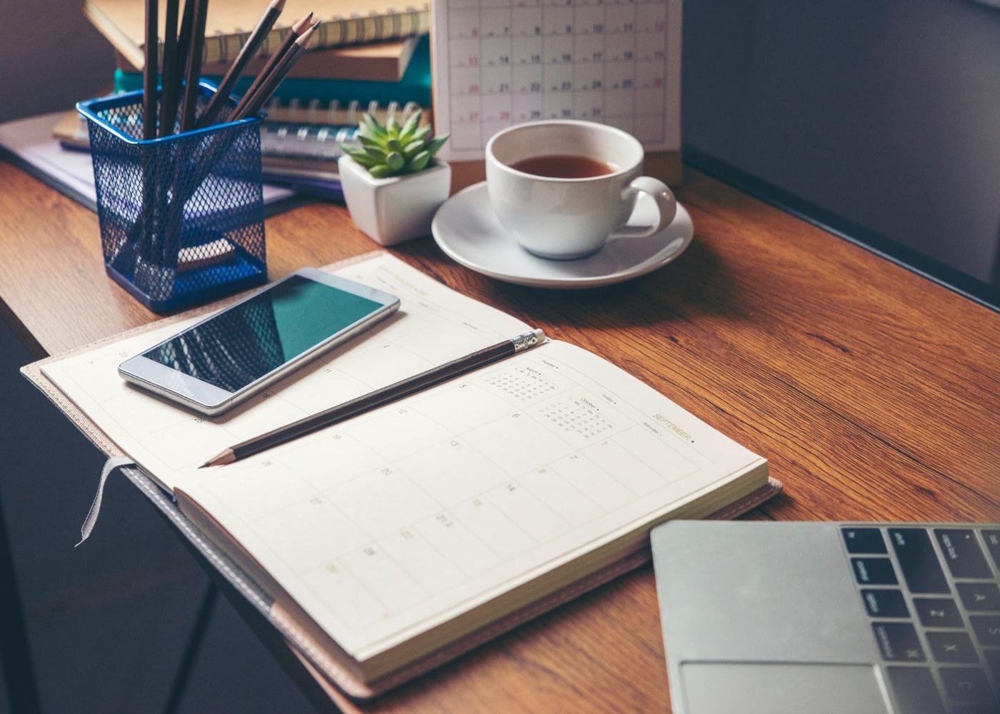 secretária com computador, telefone e agenda