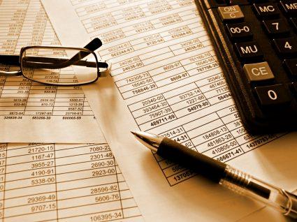 documentos, máquina de calcular, caneta e óculos dispostos em cima de uma mesa