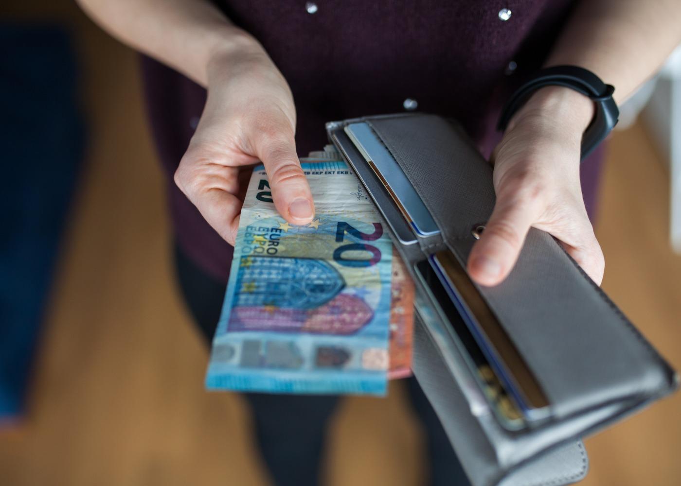 pessoa a guardar dinheiro na carteira
