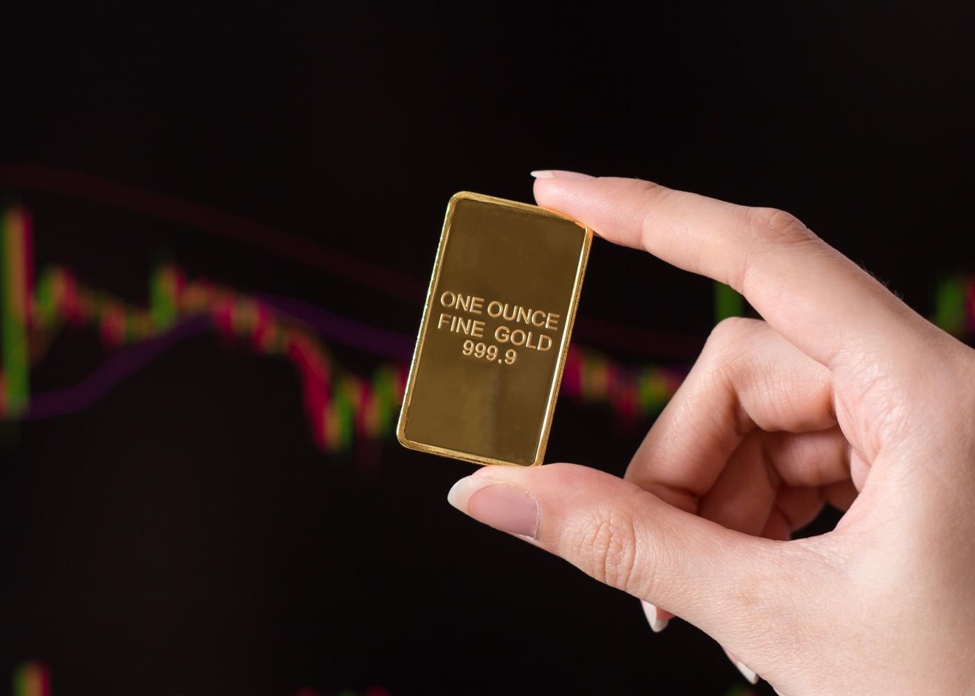 Mulher a segurar uma onça de ouro em barra