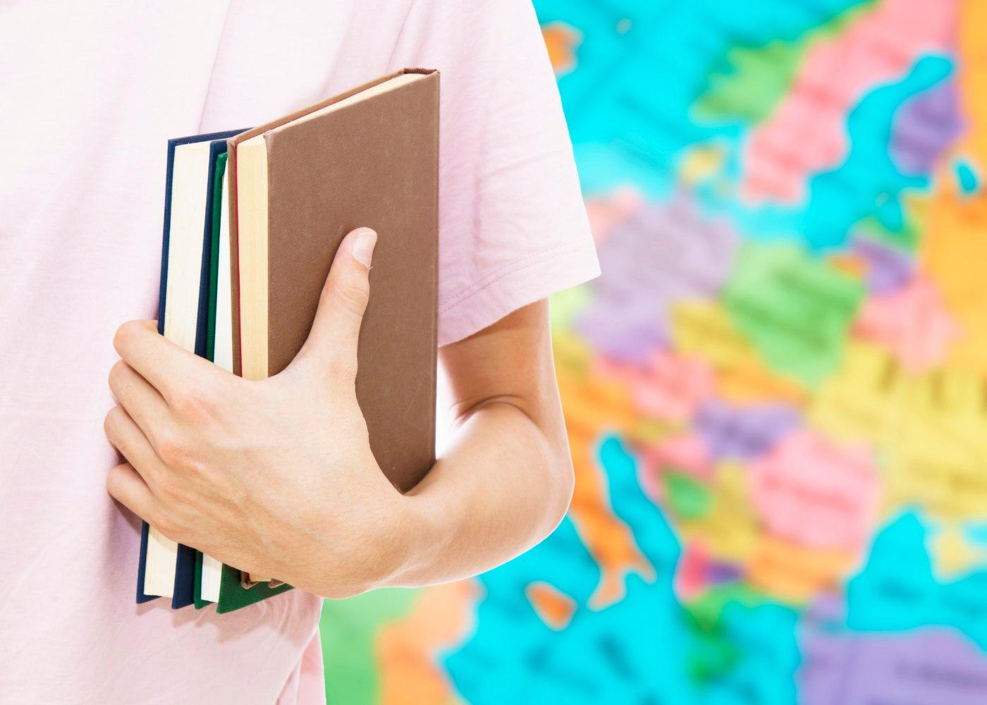 estudante a segurar livros e com mapa mundo atrás vai consultar sites gratuitos para aprender línguas