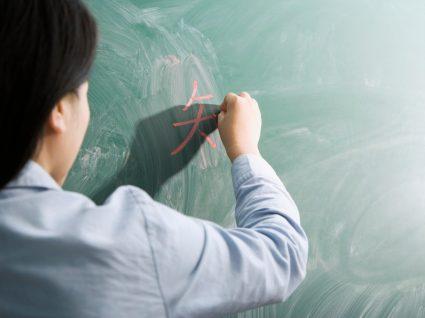 pessoa num quadro de giz a escrever em mandarim que aprendeu nos sites gratuitos para aprender línguas