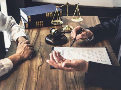 duas pessoas a analisar um contrato com símbolos da justiça em cima da mesa como o martelo de juiz, a balança e livros de códigos