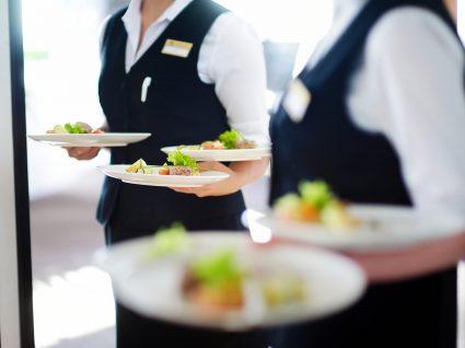 empregados de mesa com pratos na mão para servir