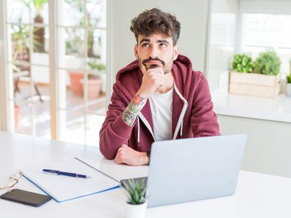 jovem estudante ao computador com ar pensativo