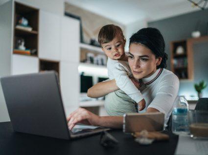 mãe com filho ao colo a pesquisar sobre se Licença de maternidade perde direito a férias