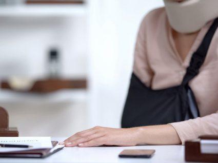 mulher a reportar acidente de trabalho com braço partido e pescoço imobilizado