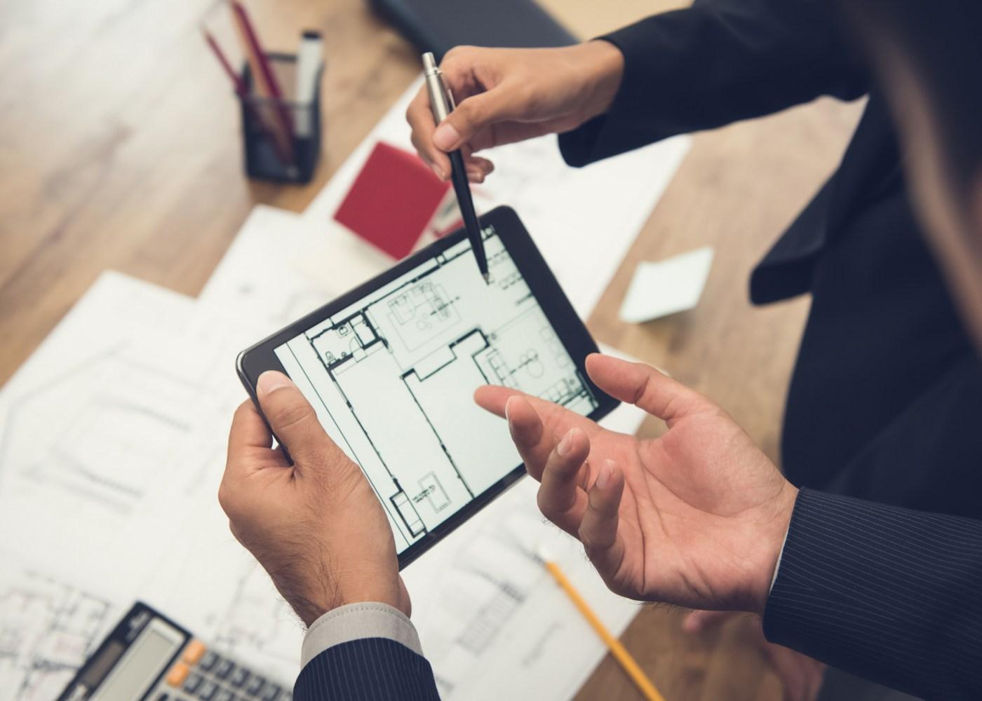 pessoas a analisar planta de uma casa num tablet