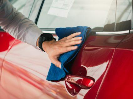 pessoa a passar pano para dar brilho ao carro