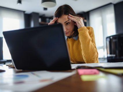 mulher com mãos na cabeça em frente ao computador