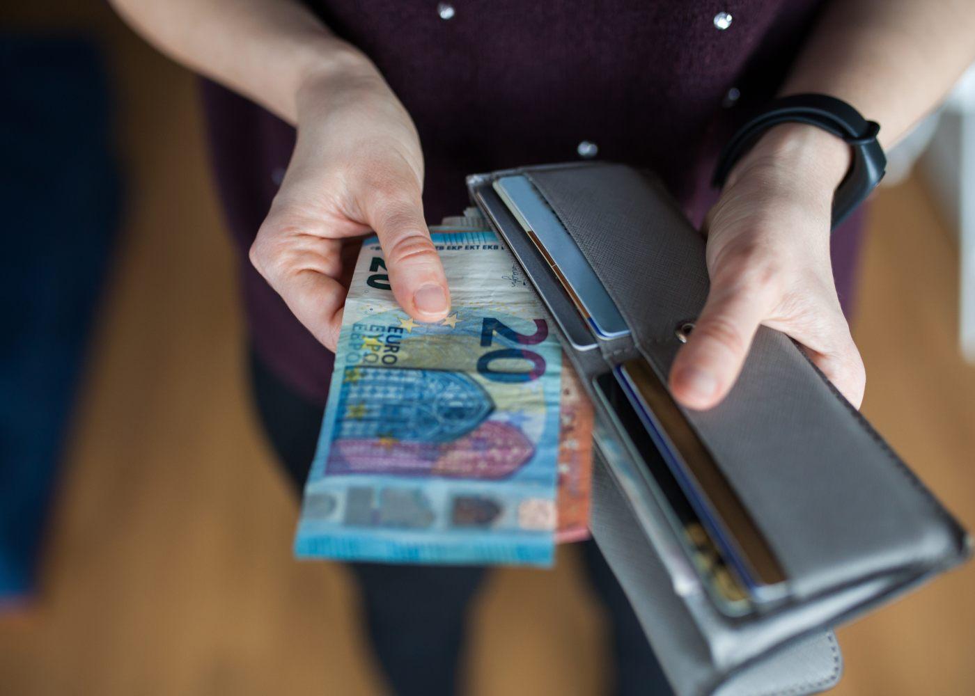 pessoa a mostrar dinheiro na sua carteira