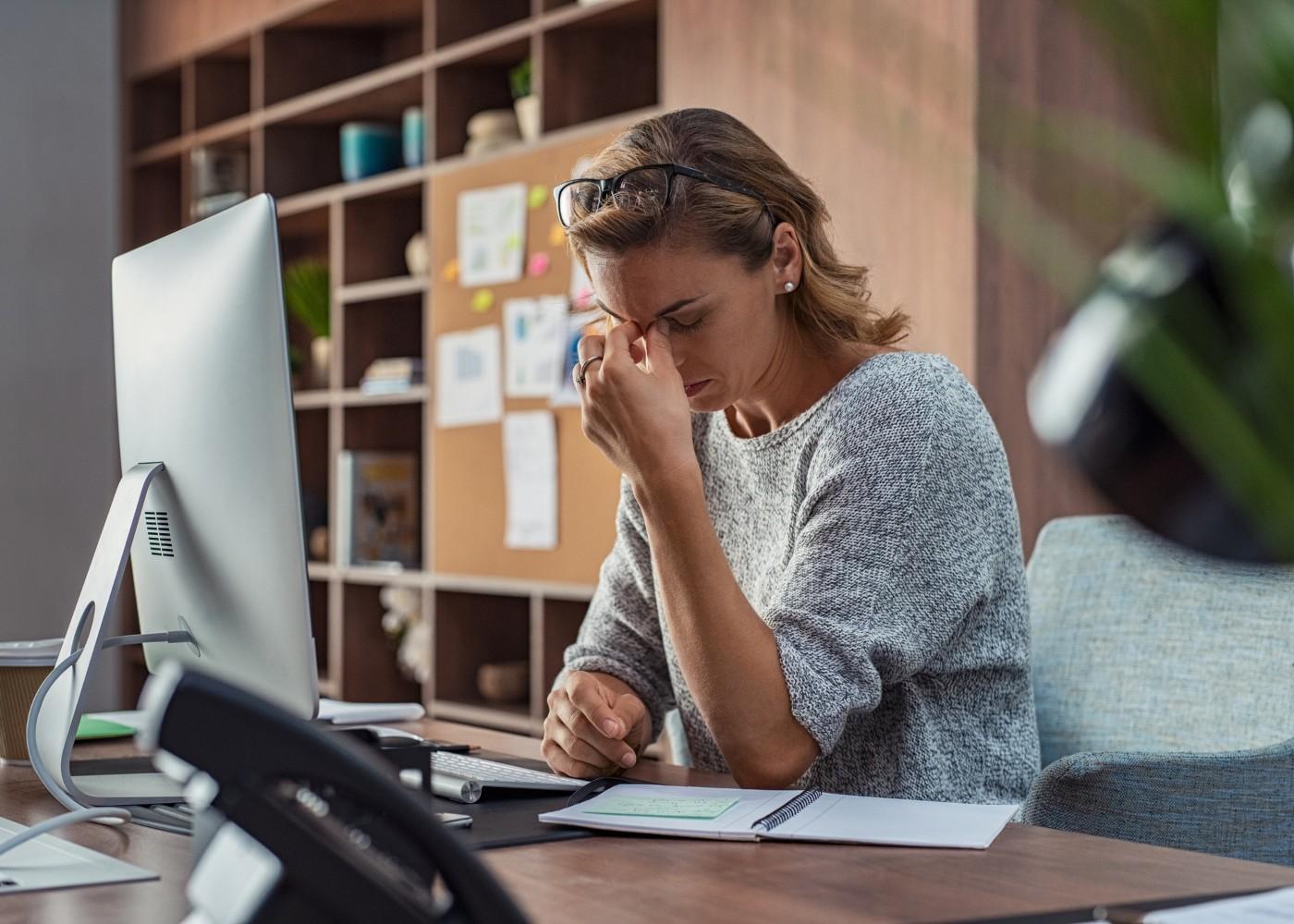 mulher ao computador com mãos na cabeça de cansaço