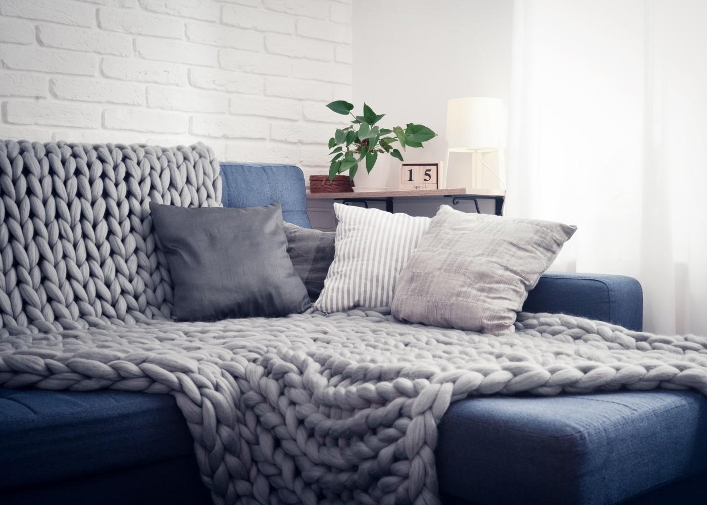 decoração de sala aconchegante com almofadas e manta no sofá