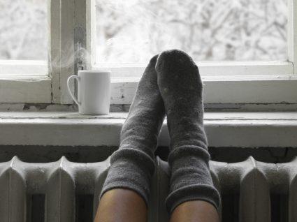 mulher com pés no aquecedor e chávena de chá na janela