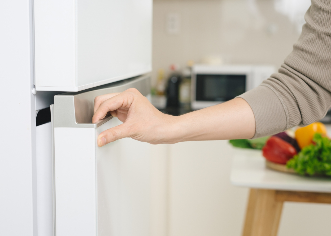Mulher a fechar porta do frigorífico