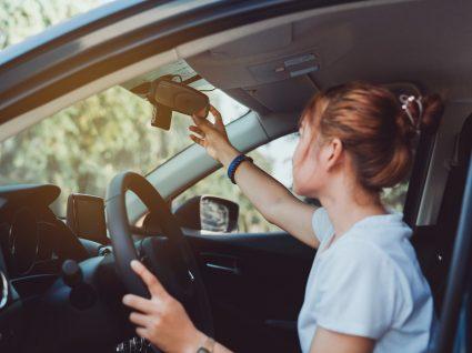 jovem condutora a ajustar espelhos