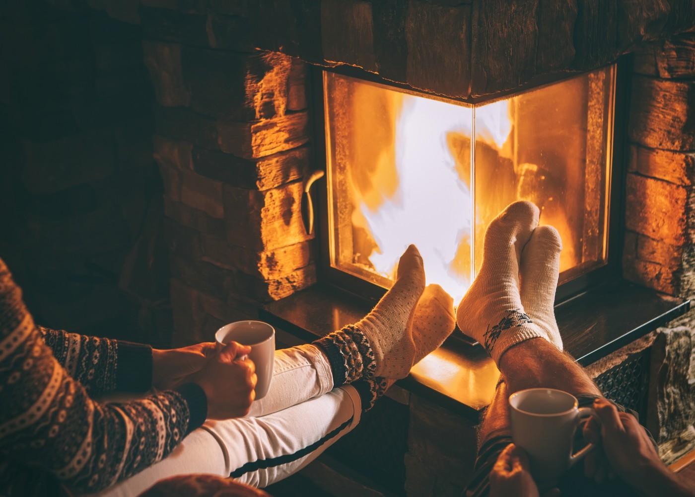 duas pessoas com pernas a aquecer com lareira