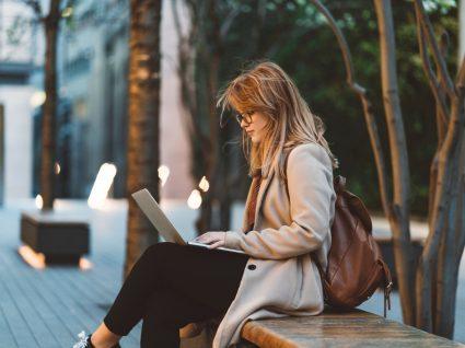 jovem sentada num banco com computador a procurar os melhores empregos para estudantes