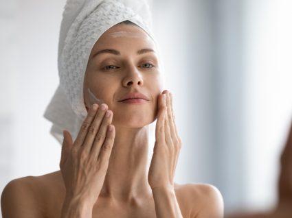 mulher a hidratar a pele seguindo a ordem de aplicação dos produtos de beleza