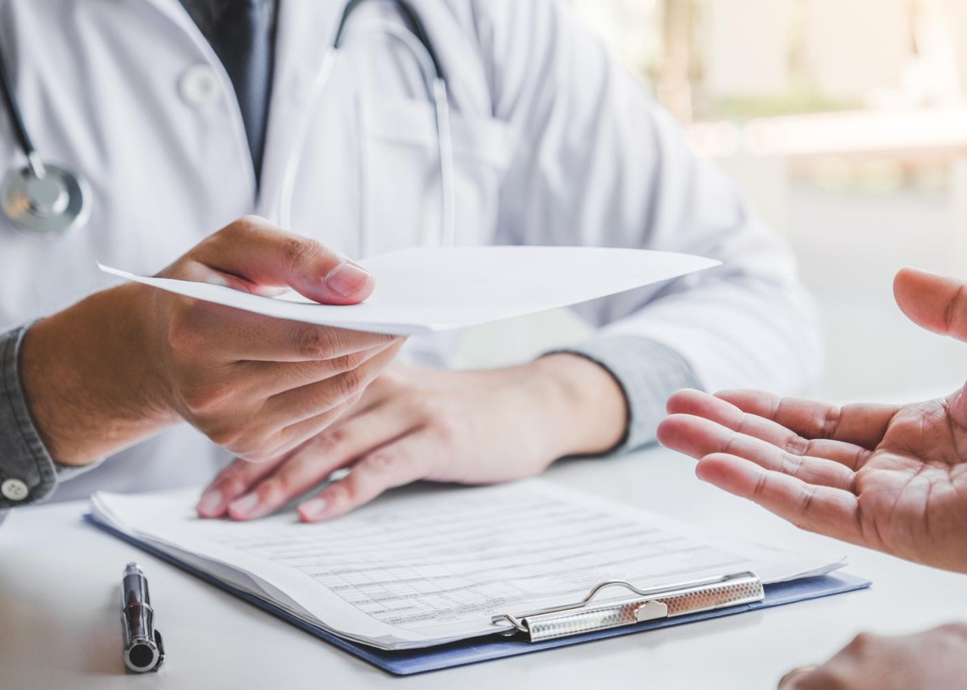 Médico a entregar receita a paciente