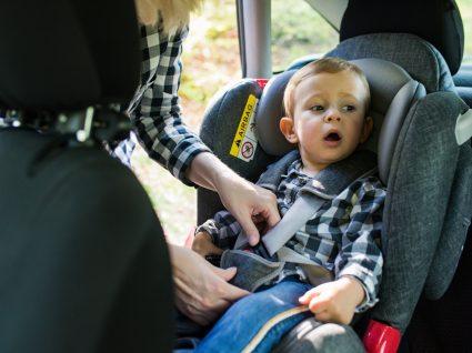 mãe a colocar filho na cadeira apropriada para transporte de crianças em automóvel seguro