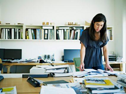 mulher a trabalhar no escritório e a ver documentos sobre a igualdade de género no trabalho