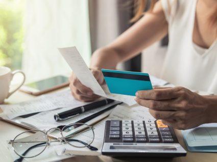 mulher a analisar cartão e recibos com máquina de calcular ao lado